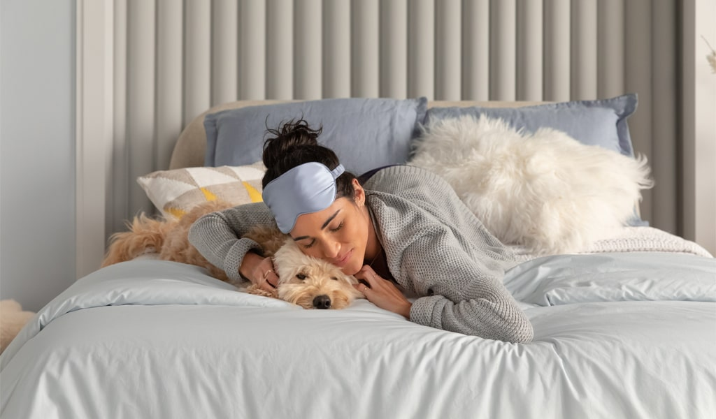 Woman sleeping with dog.